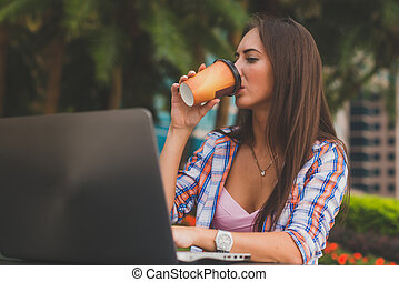Young woman drinking coffee looking at the screen of her...