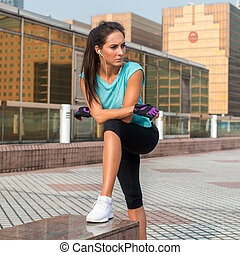 Young fit woman taking a break after exercising or running....