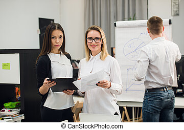 Two beautiful office workers having conversation while man colleague drawing business strategy on flip chart.