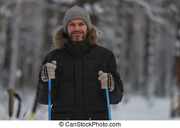 Man with ski poles in forest