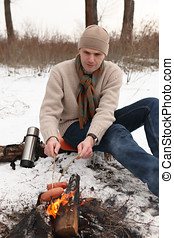 Man grilling sausages at campfire in winter