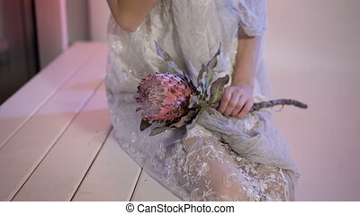 Close up of a body young girl in white wedding dress from her knees to face with creative scary and creepy halloween make. appearance sitting on the bench the flower in hands the looking at the camera.