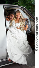 Young bride in wedding dress getting off car - Young...