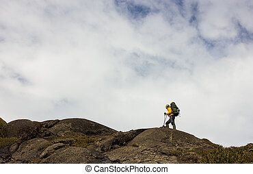 Young Lady hiker standing with backpack on top of a mountain...