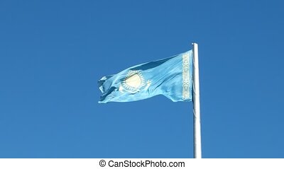 Flag of the Republic of Kazakhstan on the flagpole waving on background blue sky