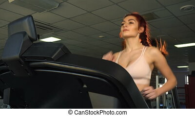Attractive caucasian girl running on the treadmill in the...