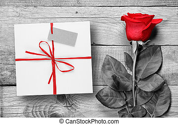 Red rose and gift box on black and white wooden background