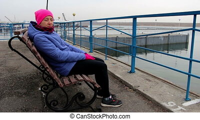 Girl sitting on a bench on the pier on a cold cloudy day...