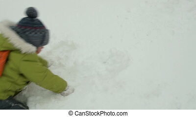 Kid making handprints in snow - Little child having fun with...