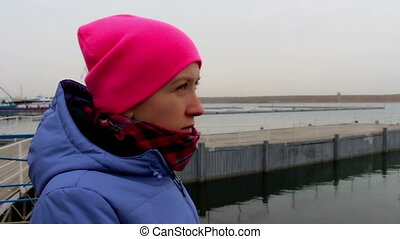 Portrait of a girl in a pink hat on the pier on a cold...
