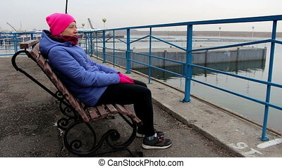 Girl sitting on a bench on the pier on a cold cloudy day and...