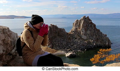 Girl sits on a rock by the sea on a background of amazing landscape, drinks tea