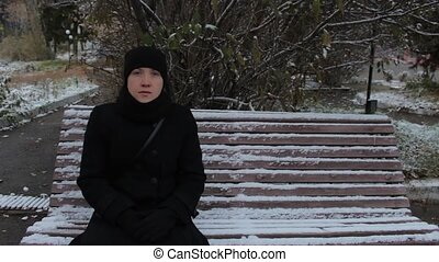 Portrait of a girl in a black dress, sitting on a bench in the park in winter