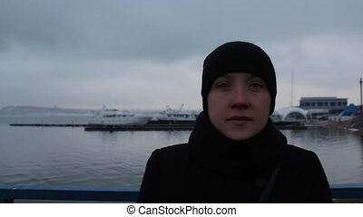 Portrait of a girl in a black dress on the pier in winter cloudy day