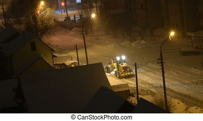 Snow removal machine cleaning road at night - Night view of...