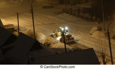 Snow plow cleaning road at night - Night view of snow...