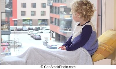 Little toddler girl looking out of window on winter day with...
