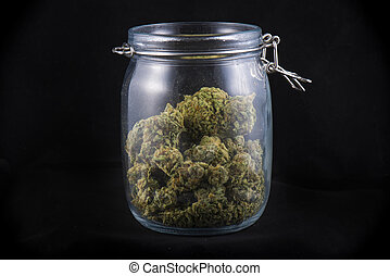 Cannabis bud in a glass jars isolated on black - medical...