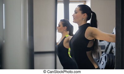 fitness coach warms up thoroughly her client in gym....