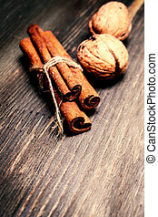 Cinnamon sticks and nuts on wooden background. Christmas...