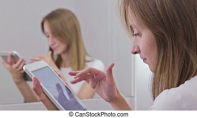 Woman using digital tablet sitting in front of mirror -...