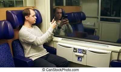 Man making photo with his smartphone in a train and sending it. 4K video