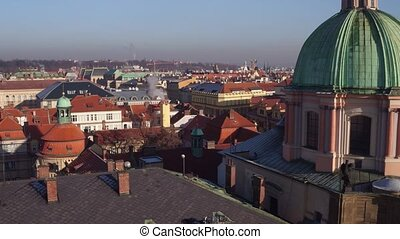 Orange roofs and gothic spires of old town and distant...