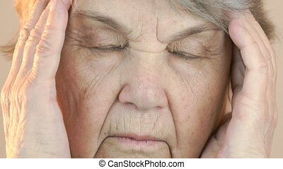 Old woman suffers from headaches. Face close up