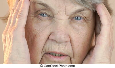 Old woman holding head with hands due to headache - Old...