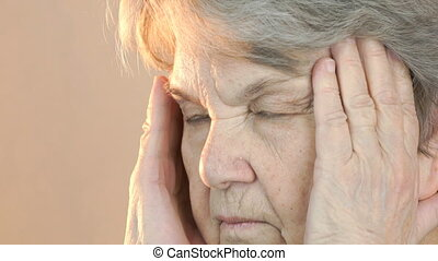 Old woman aged 80s suffers from headaches. Face close up