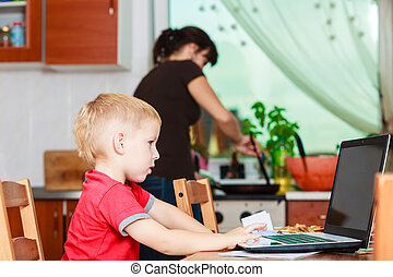 Little boy with laptop and mother cooking in kitchen. -...