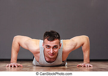 Man making pushups,dark background. Care about health