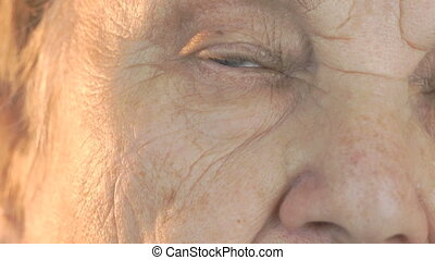 Old woman opening and closing eyes. Close up