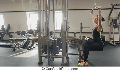 Beautiful woman works out in gym. She is dressed in black...