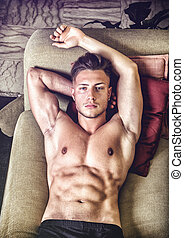 Topless young man on sofa - Shirtless sexy young man in...
