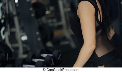 Athletic women do exercises with dumbbell in a fully-stocked...