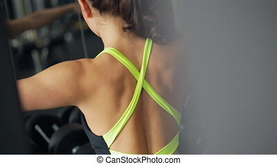 Women work with equipment in gym. View from her back.