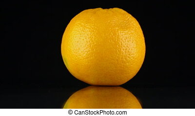 Rotating orange and its reflection on a black background....