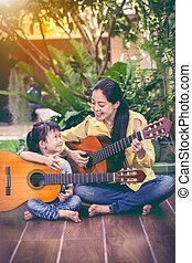 Mother with daughter play guitar. Family spending time...