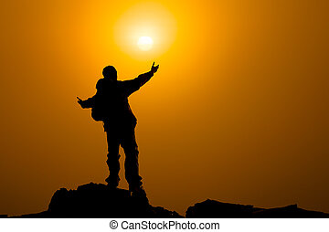 Man with arms extended toward heaven at sunrise ,success or...