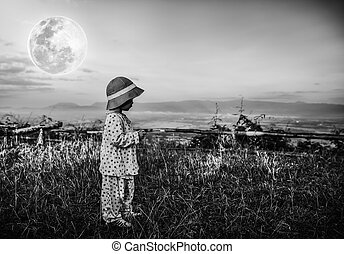Adorable girl in night sky under beautiful full moon. Black...