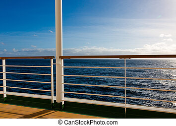 Cruise wooden deck with metal barrier in sunset rays light at Atlantic ocean