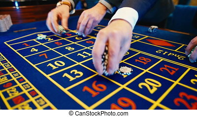Betting chips - Casino Roulette People playing Roulette in a...