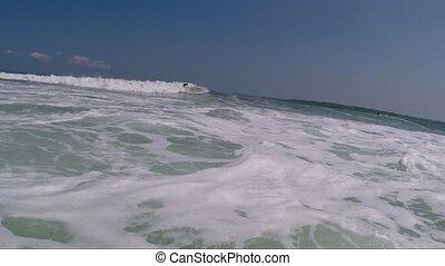 Surfer in black surfersuit on the crest of wave - Surfer on...