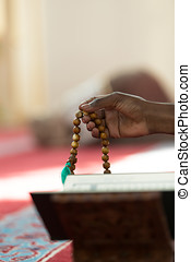 Hand of muslim black man people praying with mosque interior...