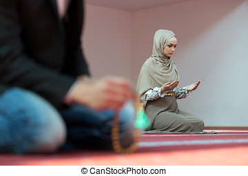 Muslim man and woman praying in mosque.