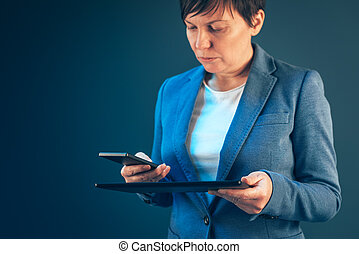 Businesswoman using mobile phone and tablet computer