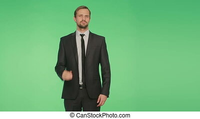 body language. a man in a business suit on a green...