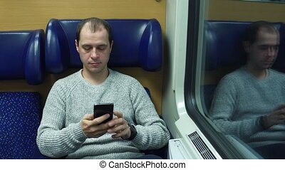 Man taking his seat in a train and typing messages in his...