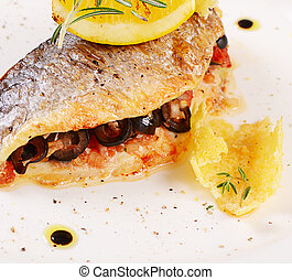 Baked fish stuffed with olives close up